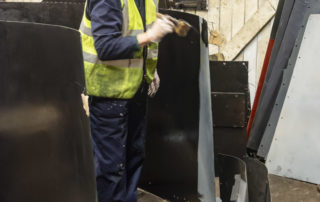 Ken Hill applies black micaceous paint to the underside of a cladding sheet. 28 February 2020 © Martyn Bane