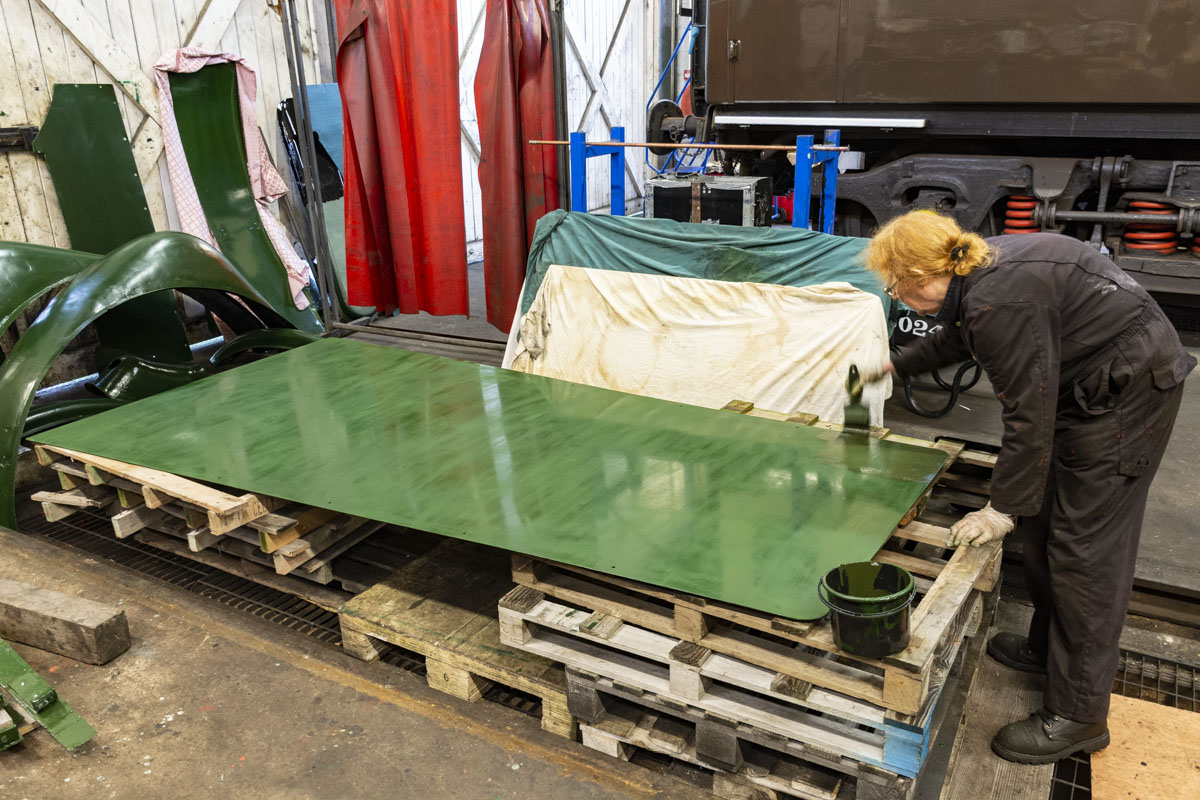 The firebox top cladding sheet, a new piece of metal, gets another coat of green paint. This large and heavy sheet will be fitted with the aid of a crane in due course. It is one of the few pieces of cladding to be replaced, the rest is fit for reuse after suitable repairs. 30 October 2020 © Martyn Bane